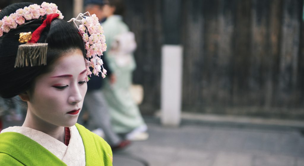 Kyoto, Japan - April 8, 2013: Portrait of a geisha approaching a tea house on Hanama koji lane in the Gion district of Kyoto. The Geisha in Gion are the highest ranked in Japan.