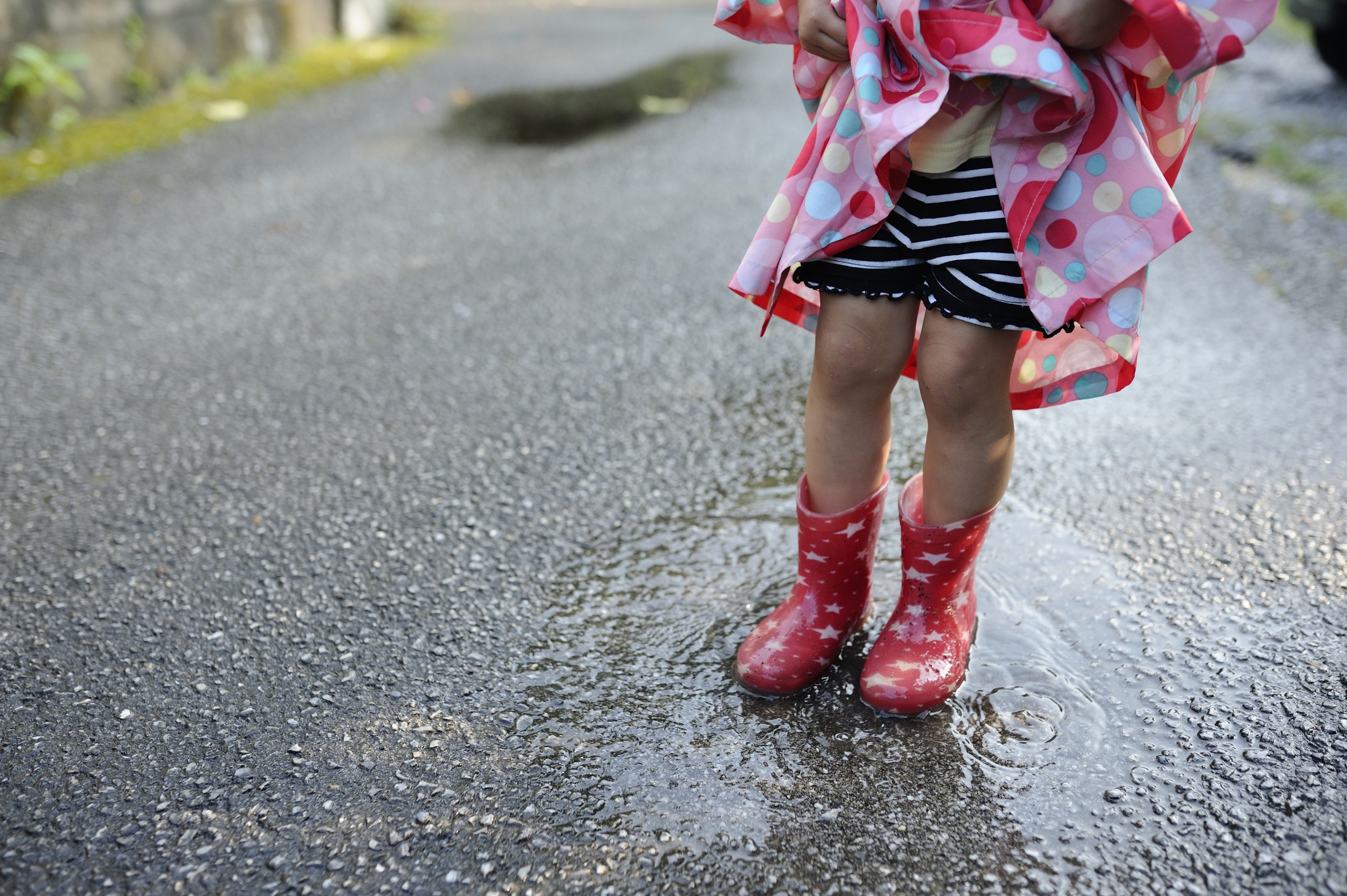 Little girl splashing in the rain.