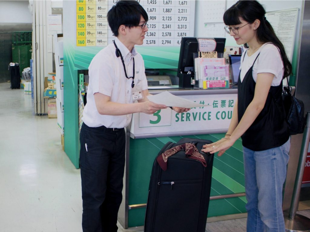 Handing over luggage at Luggage-Free Travel counter
