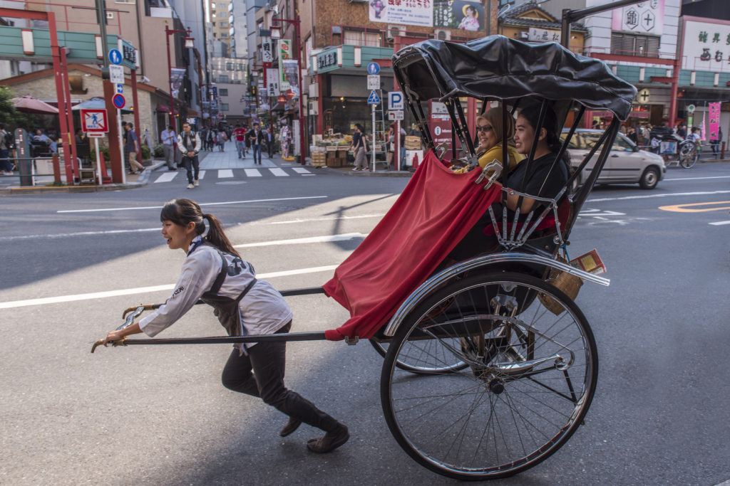 A rickshaw driver pulling tourists around Asakusa.