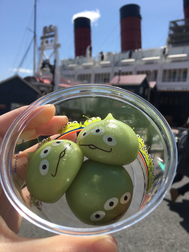 green alien mochi treat in front of the SS Columbia