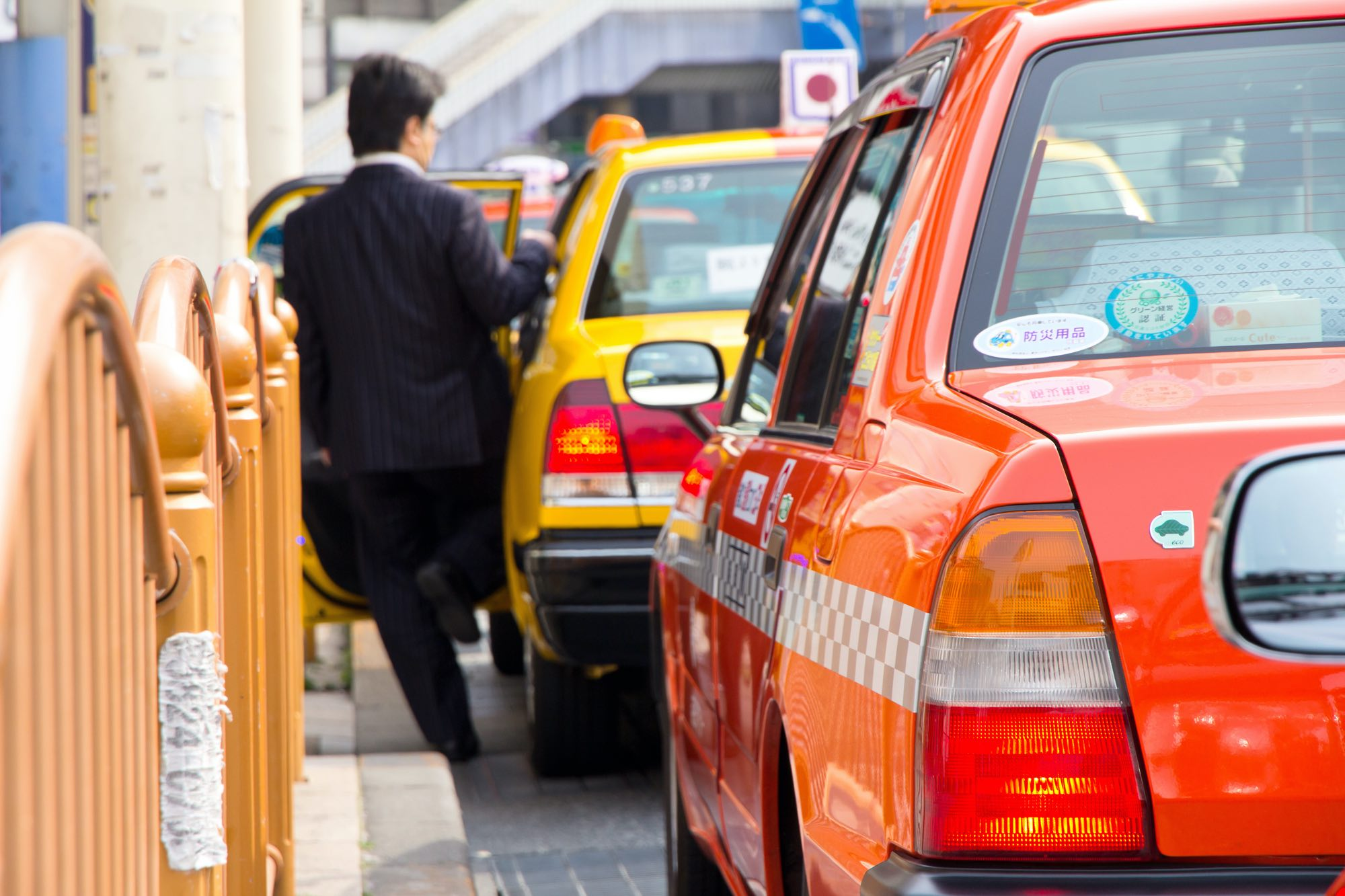 Man getting in a taxi, japanese stickers on taxis