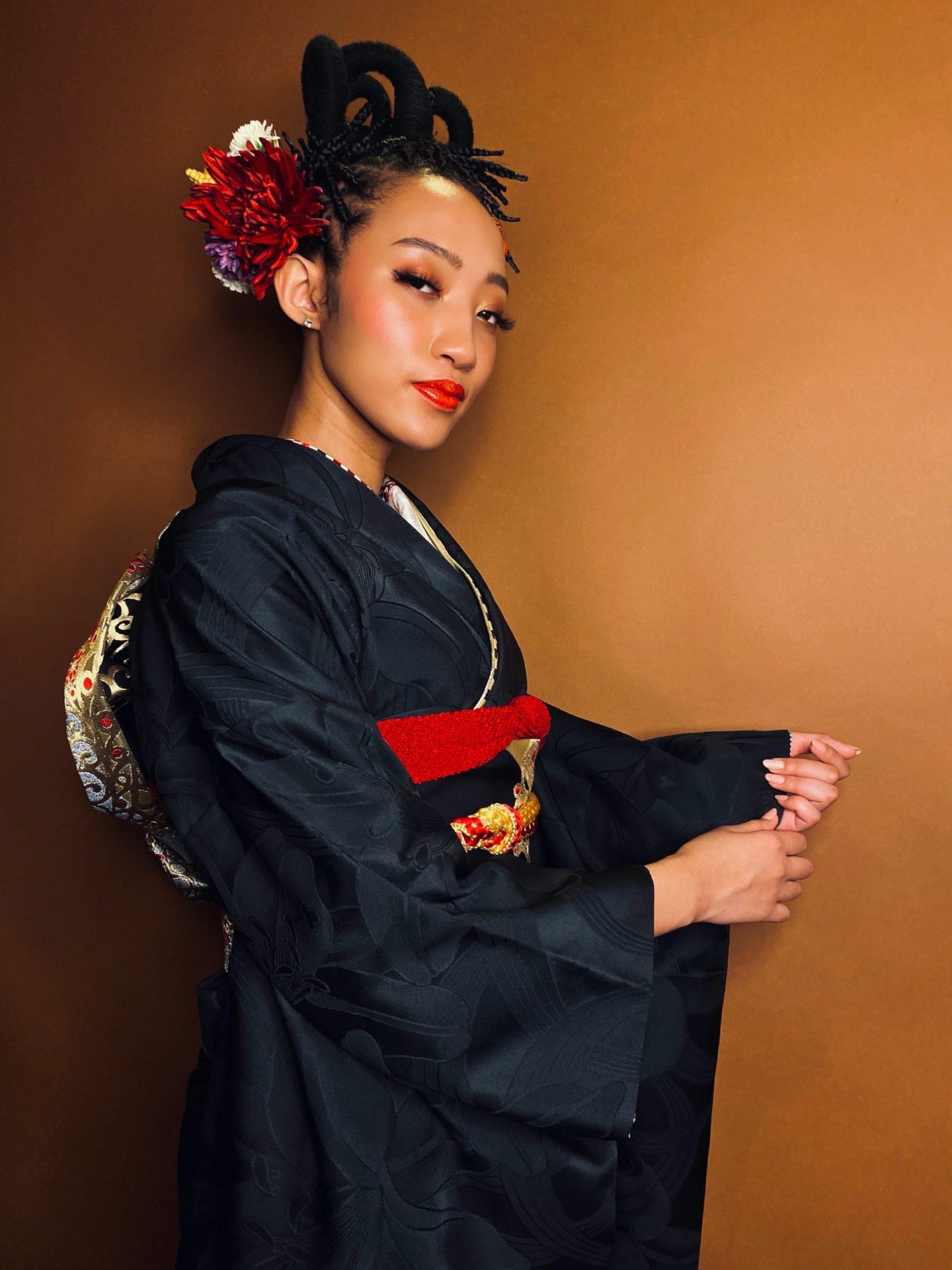 A Black model in kimono wearing braids
